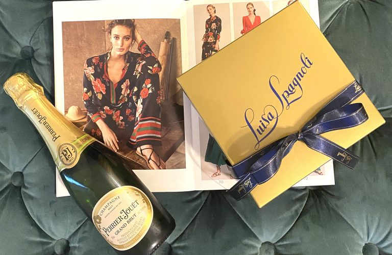 A bottle of champagne and a welcome gift from Luisa Spagnoli at Stanford Shopping Center on a cushion.